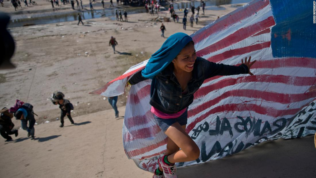 A migrant woman helps carry a handmade US flag up the riverbank at the border after getting past Mexican police in Tijuana on Sunday.