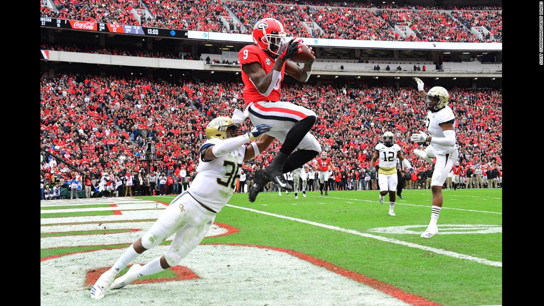Jeremiah Holloman of the Georgia Bulldogs makes a catch for a second quarter touchdown against Malik Rivera of the Georgia Tech Yellow Jackets on Saturday, November 24 in Athens, Georgia. The Bulldogs beat the Yellow Jackets 45-21.