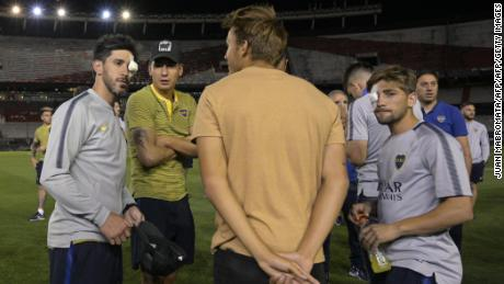 Boca Juniors' Pablo Perez and Gonzalo Lamardo are seen on the field of the Monumental stadium in Buenos Aires with their eyes covered after authorities postponed the all-Argentine Copa Libertadores final.