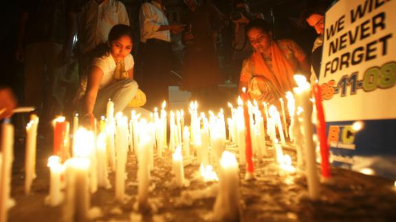 Women place candles outside the Taj Mahal Palace Hotel, in memory of the victims of the 2008 Mumbai terror attacks.