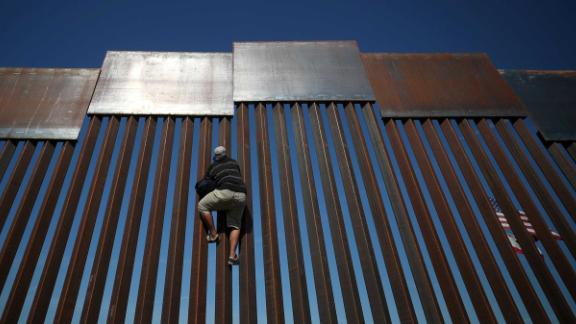 A migrant climbs the fence between Mexico and the United States.