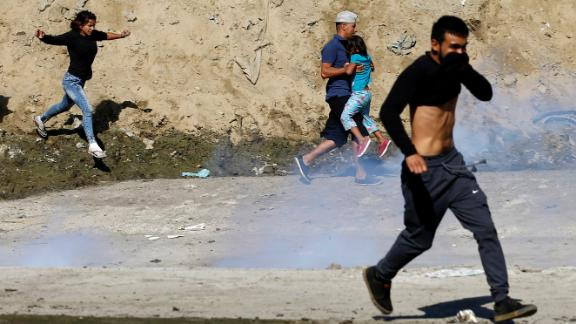 Migrants, part of a caravan of thousands traveling from Central America en route to the United States, run from tear gas released by U.S. border patrol near the fence between Mexico and the United States in Tijuana, Mexico, November 25, 2018. REUTERS/Kim Kyung-Hoon