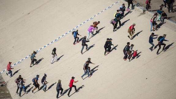 A group of migrants crosses the riverbed of the Tijuana River in an attempt to get to the port of entry.