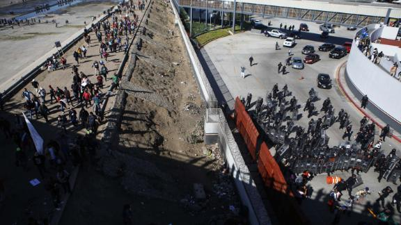 Mexican police, right, stand guard as migrants walk on a bank of the nearly dry Tijuana River. The migrants were making their way toward the El Chaparral port of entry after circumventing a police blockade.