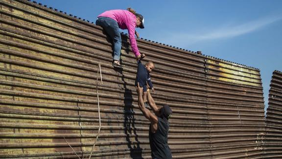 TOPSHOT - A group of Central American migrants climb the border fence between Mexico and the United States, near El Chaparral border crossing, in Tijuana, Baja California State, Mexico, on November 25, 2018. - Hundreds of migrants attempted to storm a border fence separating Mexico from the US on Sunday amid mounting fears they will be kept in Mexico while their applications for a asylum are processed. An AFP photographer said the migrants broke away from a peaceful march at a border bridge and tried to climb over a metal border barrier in the attempt to enter the United States. (Photo by Pedro PARDO / AFP)        (Photo credit should read PEDRO PARDO/AFP/Getty Images)
