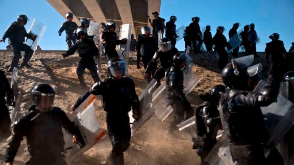Mexican police run as they try to keep migrants from getting past the border crossing in Tijuana.