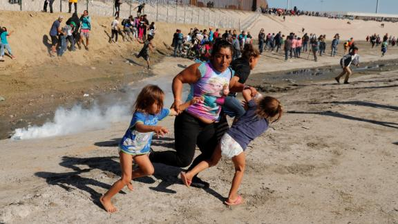 A migrant family, part of a caravan of thousands traveling from Central America en route to the United States, run away from tear gas in front of the border wall between the U.S and Mexico in Tijuana, Mexico November 25, 2018. REUTERS/Kim Kyung-Hoon     TPX IMAGES OF THE DAY