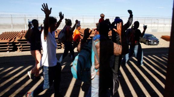 Migrants hold up their hands as US Border Patrol officers detain them. They had jumped over the border fence between Mexico and the United States.