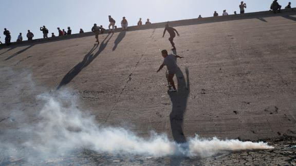 Migrants, part of a caravan of thousands traveling from Central America en route to the United States, run away from tear gas thrown by the U.S. border control near the border wall between the U.S and Mexico in Tijuana, Mexico November 25, 2018. REUTERS/Kim Kyung-Hoon