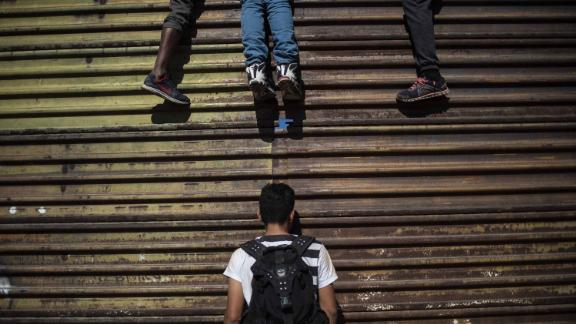 Migrants try to climb the border fence.