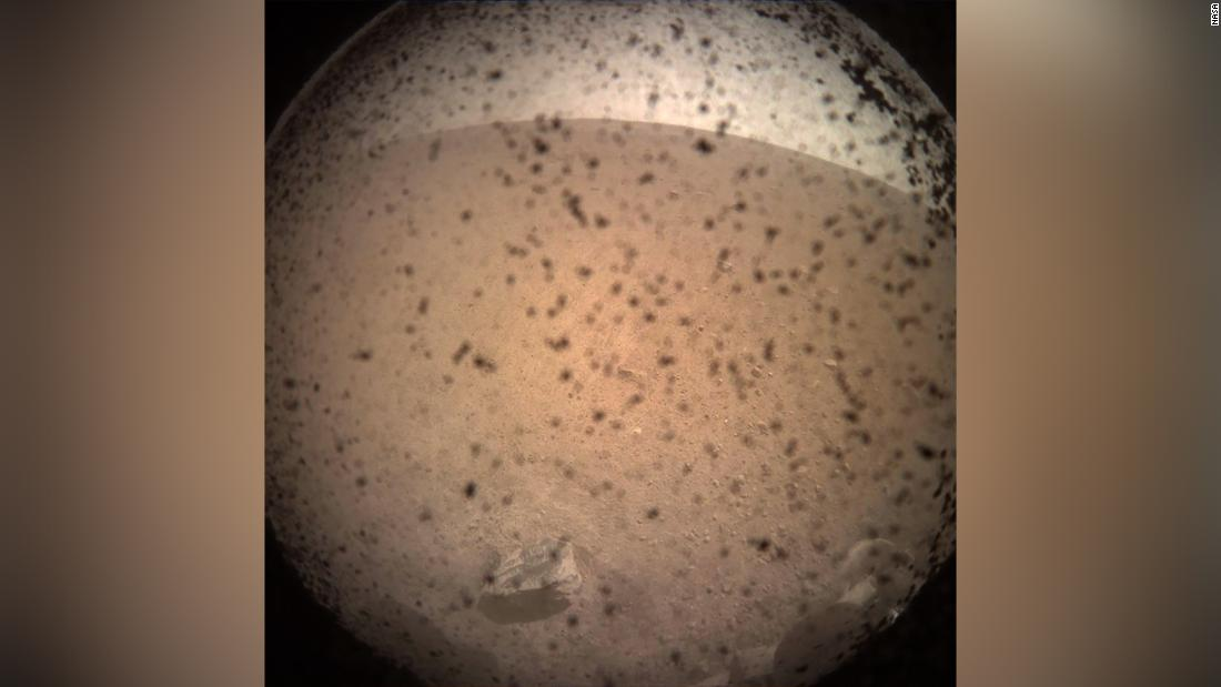 InSight's first image shortly after landing on the Martian surface on November 26, 2018.This was captured by the lander-mounted, Instrument Context Camera, with the dust shield still attached, to show the area in front of the lander.