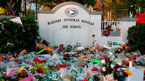 Flowers, candles and mementos sit outside one of the makeshift memorials at Marjory Stoneman Douglas High School in Parkland, Florida on February 27, 2018. Florida's Marjory Stoneman Douglas high school will reopen on February 28, 2018 two weeks after 17 people were killed in a shooting by former student, Nikolas Cruz, leaving 17 people dead and 15 injured on February 14, 2018.