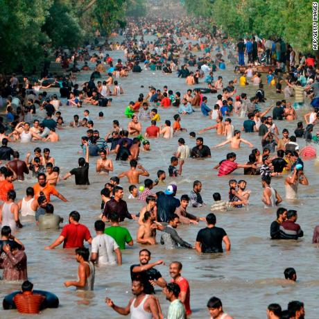 People cool themselves off in a water channel during a heat wave on June 4, 2017 in Lahore.