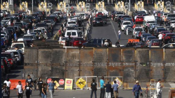 TIJUANA, MEXICO - NOVEMBER 25:  People attempting to cross in the U.S. look on as the San Ysidro port of entry stands closed at the U.S.-Mexico border on November 25, 2018 in Tijuana, Mexico. Migrants circumvented a police blockade as they attempted to approach the El Chaparral port of entry and U.S. Customs and Border Protection temporarily closed the two ports of entry on the border with Tijuana in response. Around 6,000 migrants from Central America have arrived in the city with the mayor of Tijuana declaring the situation a