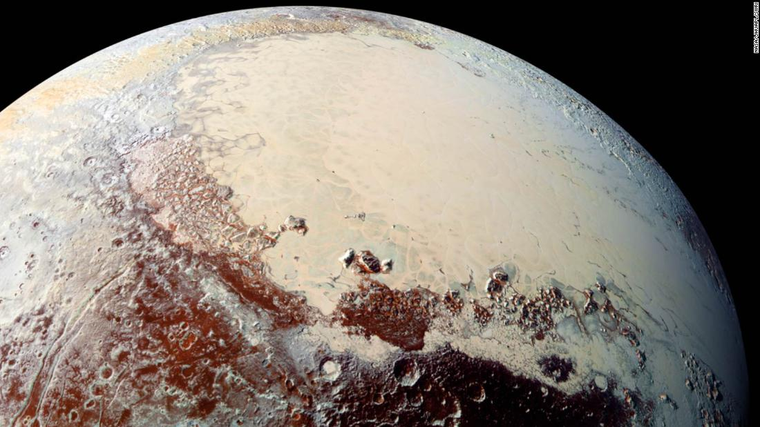 "This high-resolution image captured by NASA's New Horizons spacecraft shows Pluto's surface has a remarkable range of subtle colors, enhanced in this view to a rainbow of pale blues, yellows, oranges, and deep reds. The bright expanse is the western lobe of the ""heart,"" informally known as Tombaugh Regio. The lobe, informally called Sputnik Planum, has been found to be rich in nitrogen, carbon monoxide, and methane ices."