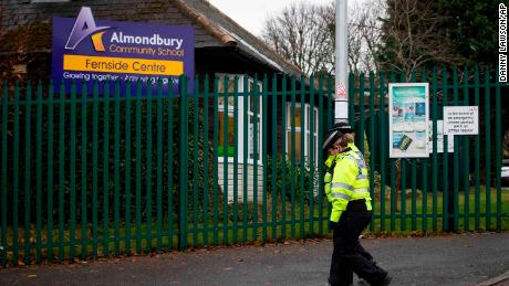 Officers on Wednesday passing the Almondbury Community School in Huddersfield, England, where police are investigating the assault of a Syrian boy.