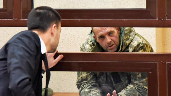 One of the captured Ukrainian sailors speaks with his lawyer in a court room Tuesday in Simferopol, Crimea.