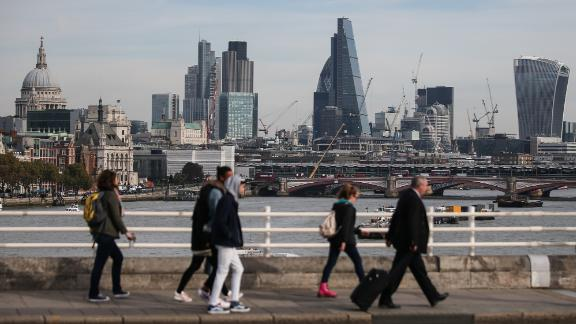 Pedestrians waling through Waterloo Bridge with the skyline of the City of London in the background on October 27, 2016.  Britain