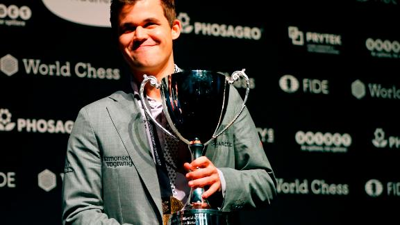 World chess champion Norway's Magnus Carlsen poses with the FIDE world chess championship trophy after beating challenger, US player Fabiano Caruana (not pictured) in the tie-break matches of the 2018 World Chess Championship in London on November 28, 2018. - Three-time defending chess champion Magnus Carlsen on Wednesday successfully defended his world title after demolishing US hopeful Fabiano Caruana in a winner-take-all finale. (Photo by Tolga AKMEN / AFP)        (Photo credit should read TOLGA AKMEN/AFP/Getty Images)