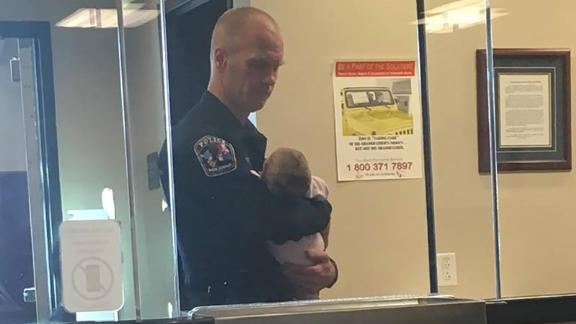 Officer Robert Lofgran cuddled an infant and watched two more children as their mother filled out paperwork for a domestic violence report.