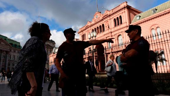 A police officer guarding the presidential palace points the way for a woman in Buenos Aires, Argentina, Wednesday, Nov. 28, 2018. Thousands of police and security agents will guard Group of 20 industrialized nations' world leaders during the two-day meeting that starts Friday. (AP Photo/Gustavo Garello)