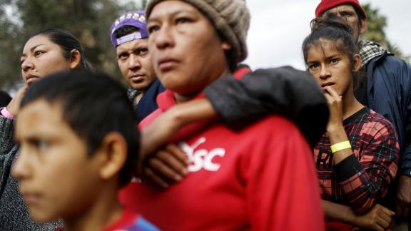 Migrants wait in line to receive donated items from a church group outside the shelter.