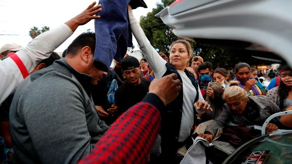 Well-wishers hand out donated clothes from the trunk of a car outside the shelter.