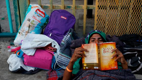 Luis Rene Reyes Garcia, a 28-year-old from Guatemala, reads a donated Bible as he rests on the street outside of the shelter.