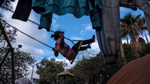 A girl rides a swing at the shelter.