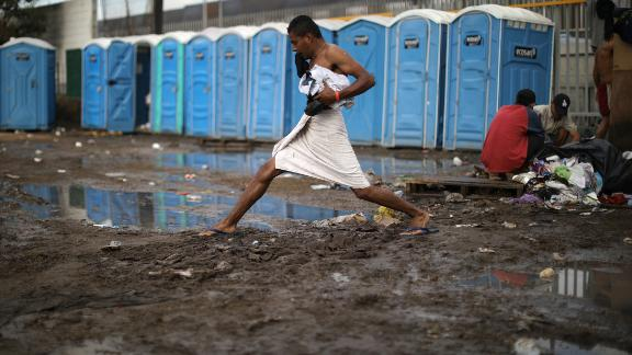A man steps across mud after taking a shower at the shelter.