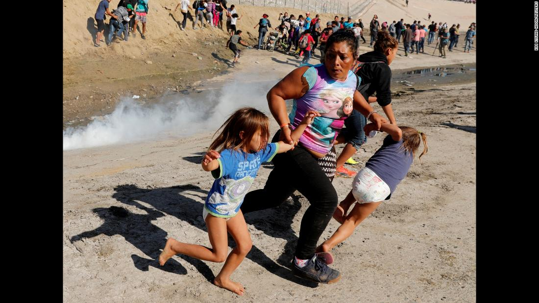"Migrant Maria Meza and her 5-year-old twin daughters, Saira Mejia Meza and Cheili Mejia Meza, run from tear gas that was deployed by US Border Patrol agents near the fence between Mexico and the United States on Sunday, November 25. The tear gas was fired after some migrants on the Mexican side of the border <a href=""https://www.cnn.com/2018/11/25/americas/gallery/migrant-border-1125/index.html"" target=""_blank"">overran police</a> and tried to cross the border. The incident marked an escalation of tensions that have been mounting since groups of Central American migrants began arriving in the Mexican border city of Tijuana, drawing threats from US President Donald Trump to close the border."