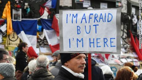 "A man holding a placard reading ""I am afraid but I am here"" during a gathering on Place de la Republique (Republic square) on January 10, 2016 in Paris, as the city marks a year since 1.6 million people thronged the French capital in a show of unity after attacks on the Charlie Hebdo newspaper and a Jewish supermarket. Just as it was last year, the vast Place de la Republique is the focus of gatherings as people reiterate their support for freedom of expression and remember the other victims of what would become a year of jihadist outrages in France, culminating in the November 13 coordinated shootings and suicide bombings that killed 130 people and were claimed by the Islamic State (IS) group. DOMINIQUE FAGET/AFP/Getty Images"