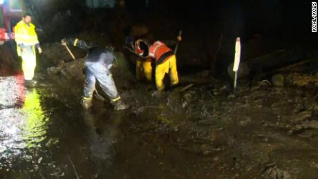 Workers in Malibu, California, shovel sludge from a road during heavy rains Thursday.