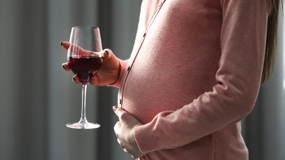 Pregnant woman with glass of red wine in hand