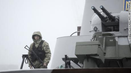 Ukrainian soldiers patrol a military boat