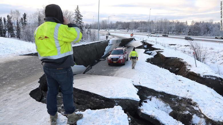 A stranded vehicle sits on a collapsed roadway near the Anchorage airport after the 7.0 earthquake.