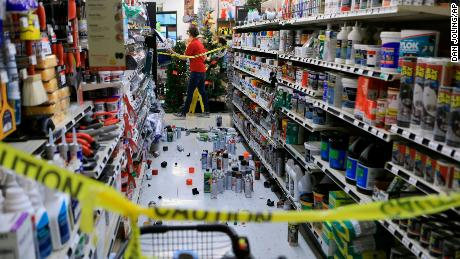 An employee walks past a damaged corridor in an Anchorage True Value hardware store.
