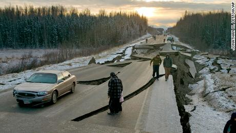 People walk along a road in Wasilla after Friday's earthquake.