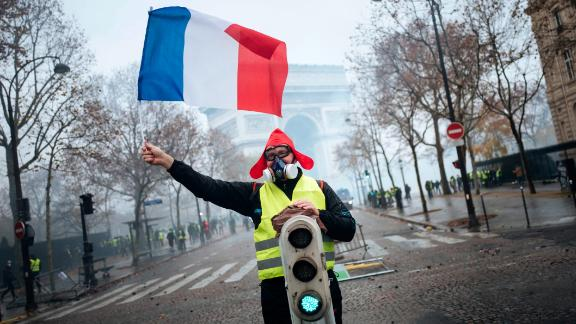 A demonstrator holds a French flag near the Arc de Triomphe during a demonstration Saturday, Dec.1, 2018 in Paris. Paris police say at least 63 people have been arrested in violent clashes between protesters and police amid nationwide demonstrations against rising taxes and President Emmanuel Macron's policies. (AP Photo/Kamil Zihnioglu)