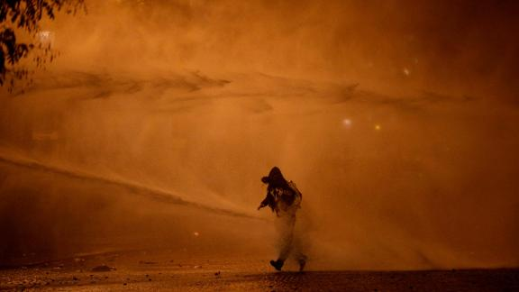 A demonstrator leaves as water cannons evacuate the Place de l'Etoile on  Saturday, December 1, in Paris.