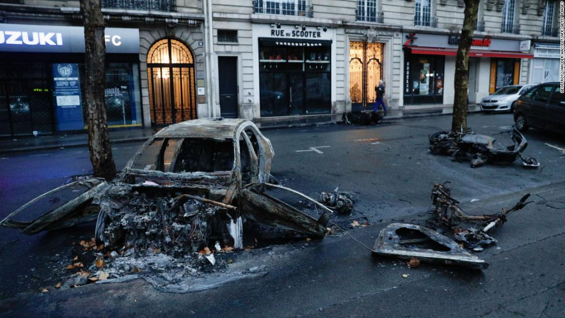 A burned car is left in the street a day after the  yellow vests demonstration against rising oil prices and living costs in Paris on December 1.