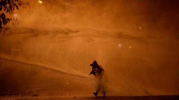 A demonstrator leaves as water cannons evacuate the Place de l