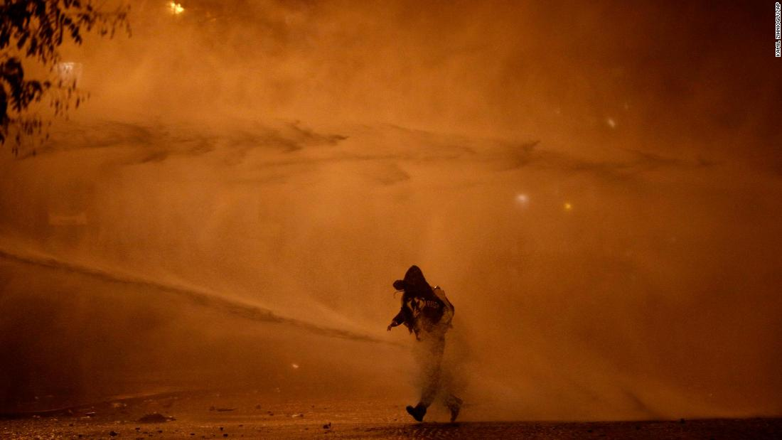 A demonstrator leaves as water cannons evacuate the Place de l'Etoile on December 1.