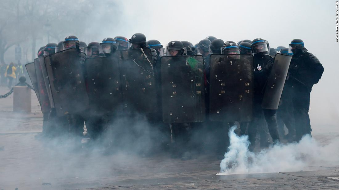 Riot police officers stand in position during clashes with demonstrators on December 1.