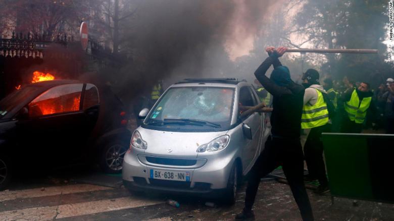 Hooded demonstrators smash a car.