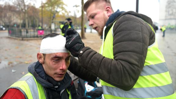 A demonstrator treats a wounded man during a protest where police and demonstrators clashed, injuring dozens on December 1.