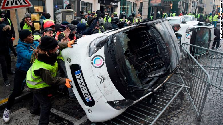 Demonstrators destroy cars.