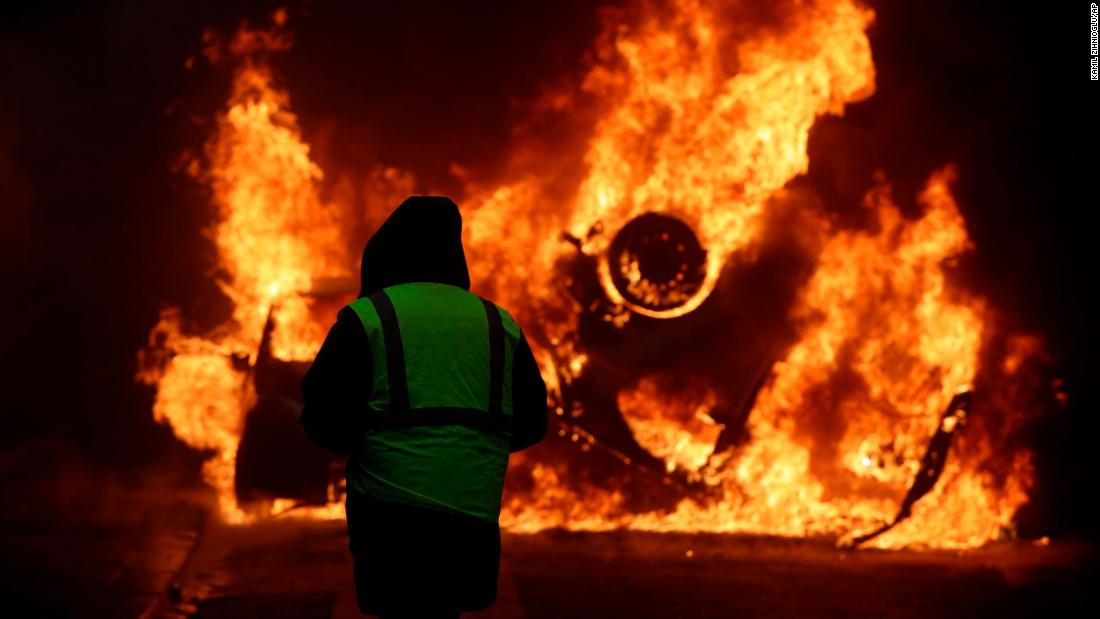 A demonstrator watches a burning car near the Champs-Elysees avenue on December 1.