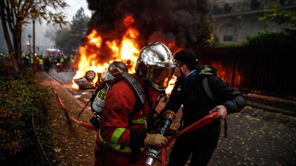 Firemen work to extinguish a burning car on December 1.