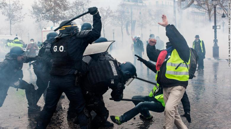 "Protesters and riot police clash during the ""yellow vest"" protests in Paris on December 1."